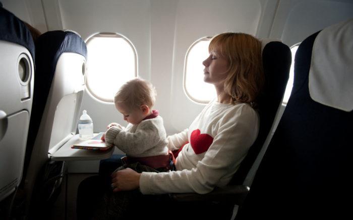 ребенок на руках у мамы в самолете